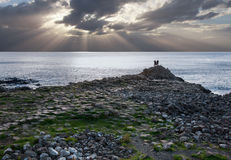 Giants Causeway, tourist silhouettes and sun beams Royalty Free Stock Image