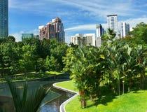 Giardini della città con i grattacieli Immagine Stock