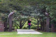 Giardini di Lauritzen, Omaha, Nebraska, donna che cammina sotto un tunnel degli alberi immagini stock