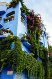 Giardini Naxos blue hotel covered in greenery, Sicily. Blue hotel covered in greenery and flowers in picturesque old town of Giardini Naxox, Sicily, Italy Royalty Free Stock Images