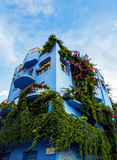 Giardini Naxos blue hotel covered in greenery, Sicily. Blue hotel covered in greenery and flowers in picturesque old town of Giardini Naxox, Sicily, Italy Stock Photos