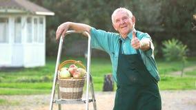 Giardiniere anziano che mostra pollice su video d archivio