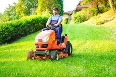 Giardiniere che guida una falciatrice da giardino di guida in giardino fotografia stock