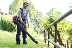 Giardiniere che riordina le foglie facendo uso di un ventilatore di foglia immagine stock