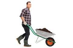 Giardiniere che spinge una carriola in pieno di sporcizia fotografia stock libera da diritti