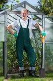 Giardiniere che sta davanti alla serra Fotografia Stock