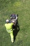 Giardiniere che taglia l'erba immagini stock