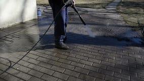 Giardiniere con il getto di rifiuti del lavaggio dell'acqua dalle mattonelle