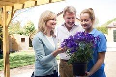 Giardiniere di paesaggio Advising Mature Couple sulle piante di giardino Fotografie Stock Libere da Diritti