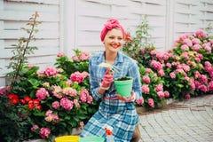giardiniere felice della donna con i fiori Cura ed innaffiatura del fiore suoli e fertilizzanti Fiori della serra cura della donn fotografia stock