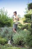 Giardiniere sveglio che odora le erbe organiche Fotografie Stock