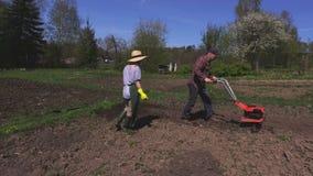 Giardinieri che elaborano suolo di estate stock footage