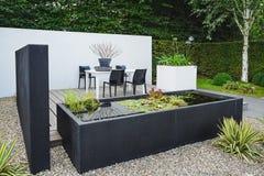 Giardino con mobili da giardino moderni e lo stagno d'avanguardia Fotografia Stock Libera da Diritti
