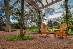 Giardino del gazebo con le sedie di legno fotografie stock libere da diritti