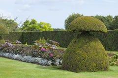 Giardino dell'ars topiaria con i fiori, alberi, barriera alta Fotografie Stock Libere da Diritti
