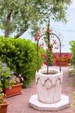 Giardino di fiore con il pozzo della pietra Immagine Stock Libera da Diritti