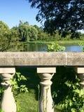 Giardino inglese - recinto concreto del piedistallo che trascura un lago fotografie stock