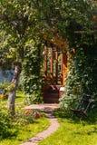 Giardino sbocciante con la vista su una veranda Fotografie Stock Libere da Diritti