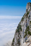Gibraltar cliff face above clouds on sky. Royalty Free Stock Photos