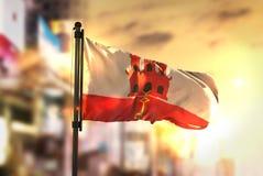 Gibraltar Flag Against City Blurred Background At Sunrise Backli. Ght Royalty Free Stock Photo