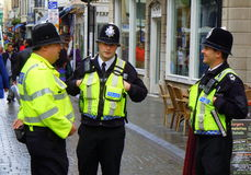 Three policemen in helmets talking in street Stock Image