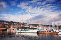 Gibsons Harbour. A sailing yacht moored in Gibsons Harbour in British Columbia, Canada. behind are many more moored leisure craft and fishing vessels. A family Stock Photos