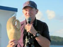 Gids die een zeekreeftklauw in een sightseeingsboot tonen Royalty-vrije Stock Fotografie