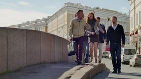 Gids met de gang van de toeristengroep langs dijk op achtergrond van oude cityscape stock video