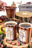 Gießen aus dem Kessel für Tee durch ein Sieb in zwei Schalen Lizenzfreie Stockfotos