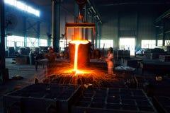 Gießen des flüssigen Metalls in der Werkstatt des geöffneten Herds Stockfotografie