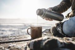 Gießen des Tees von der Thermosflasche Stockfotografie