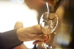 Gießen eines Glases Weißweins Stockfotos