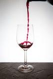 Gießen eines Glases Weins Stockbild