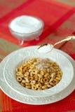 Gießen eines Spoonful Zuckers auf Multi-Korn Getreide in einem weißen Chi Stockbild