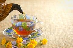 Gießen Sie den Tee in einen Becher vom Kessel Stockfotografie