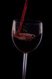 Gießen Sie den Wein in das Glas auf einem schwarzen Hintergrund Stockfotos