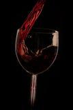 Gießen Sie den Wein in das Glas auf einem schwarzen Hintergrund Lizenzfreies Stockbild