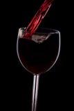 Gießen Sie den Wein in das Glas auf einem schwarzen Hintergrund Lizenzfreies Stockfoto