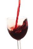 Gießen Sie den Wein in das Glas auf einem weißen Hintergrund Lizenzfreies Stockbild