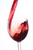 Gießen Sie den Wein in das Glas auf einem weißen Hintergrund Lizenzfreie Stockbilder