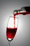 Gießen Sie den Wein in ein Glas Stockbilder