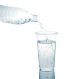 Gießen Sie in ein Glas, das auf einem weißen Hintergrund lokalisiert wird. Stockbild