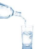 Gießen Sie in ein Glas, das auf einem weißen Hintergrund lokalisiert wird. Stockfotos