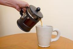 Gießen Sie Kaffee in Kaffeetasse von der Kaffeemaschine Lizenzfreies Stockbild
