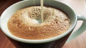 Gießen Sie Milch in einen Kaffee stock footage