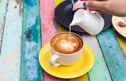 Gießen Sie Milch zur Kaffeetasse Stockfoto