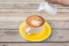 Gießen Sie Milch zur Kaffeetasse im hölzernen Hintergrund Stockbilder