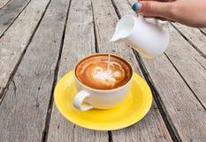 Gießen Sie Milch zur Kaffeetasse im hölzernen Hintergrund Stockfotos