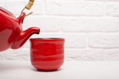 Gießen Sie Tee in eine rote Schale lizenzfreies stockfoto