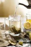 Gießen Sie Tee von einer Teekanne in einen Becher Sind auf dem Tisch Zitronen und Trauben Uhr als Kaffeetasse, Zeitung und Stift stockfotografie